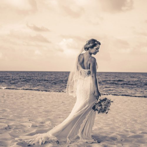 Bride on beach with dress flowing in the wind at Secrets Playa Mujeres, Cancun Mexico