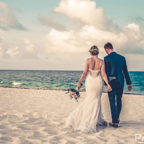 Bride and groom walking away on beach after wedding at Secrets Playa Mujeres in Cancun Mexico