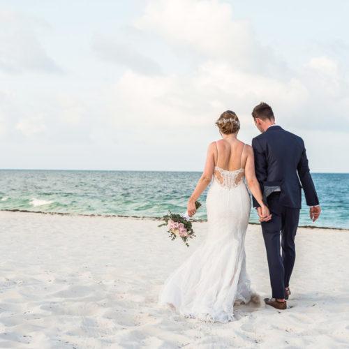 Bride and groom walking on beach at Secrets Playa Mujeres resort