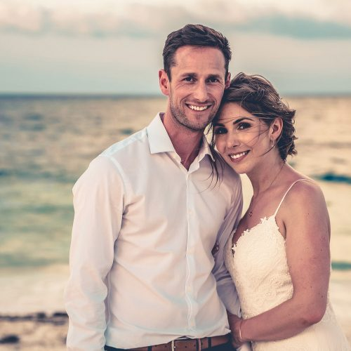 Casual portrait of bride and groom on beach