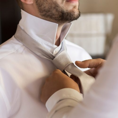 Groom doing up tie at wedding at NOW Sapphire Riviera Maya Resort