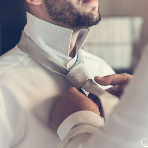 Best man doing up grooms tie.