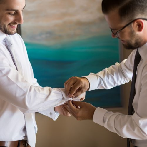 Groomsman helping groom.