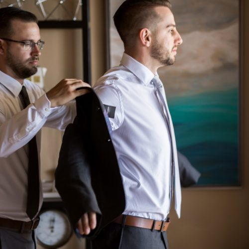 Groomsman helping groom put on jacket at NOW Sapphire Riviera Maya Resort