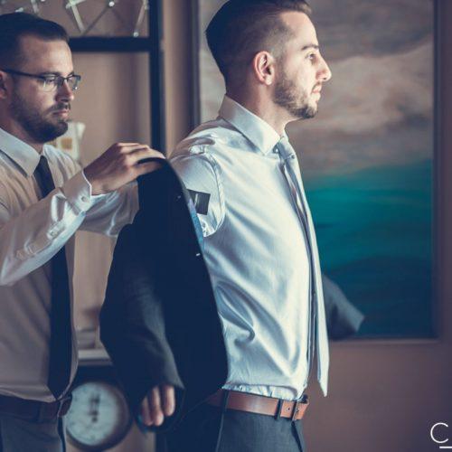 Best man helping groom get ready.