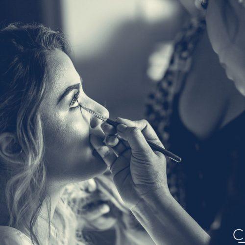 Bride having her makeup done before wedding.