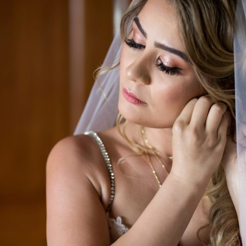 Bride putting on ear ring.
