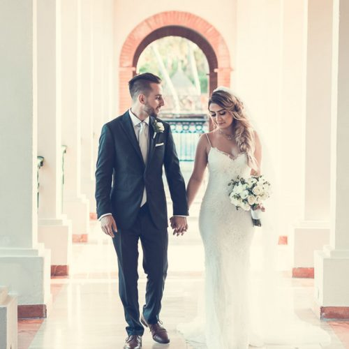 Bride and groom walking down hallway at NOW Sapphire Riviera Cancun resort