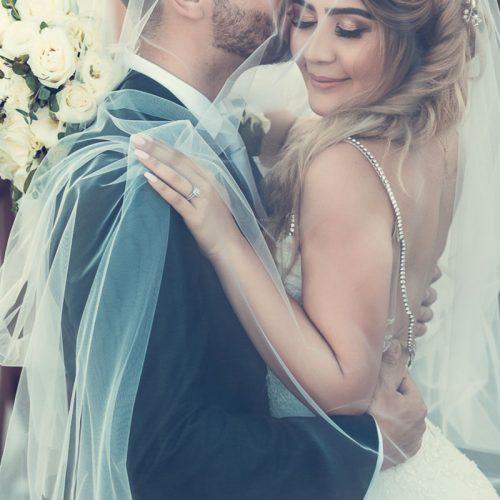 Bride and groom under veil kissing.
