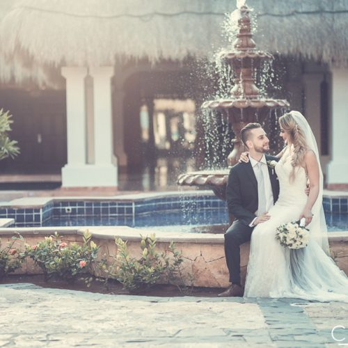 Bride and groom beside fountain at NOW Sapphire Riviera Cancun resort