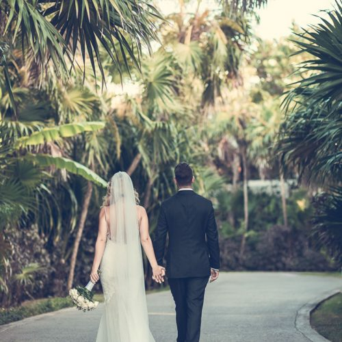 Bride and groom walking away in gardens at NOW Sapphire Riviera Cancun resort