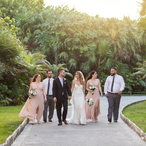 Bridal party walking on path in gardens at Bride in gardens at NOW Sapphire Riviera Maya Resort