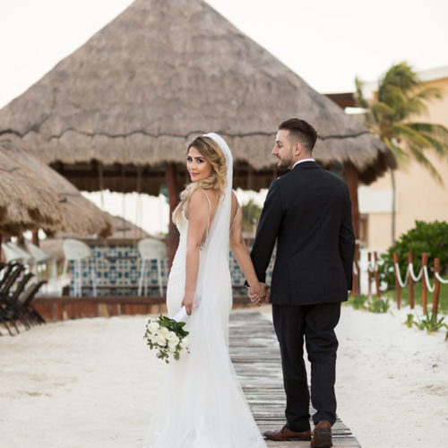 Bride and groom walking on boardwalk at Bride in gardens at NOW Sapphire Riviera Maya Resort