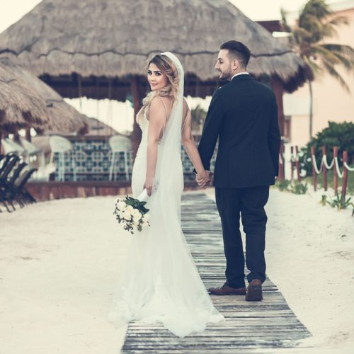 Bride and groom walking on wooden path at NOW Sapphire Riviera Cancun resort