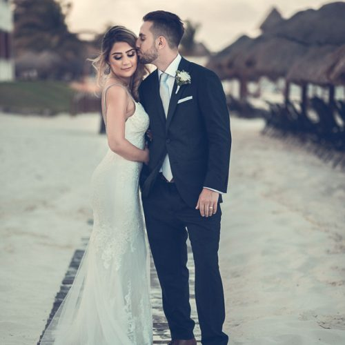 Groom kissing bride on wooden path at NOW Sapphire Riviera Cancun resort