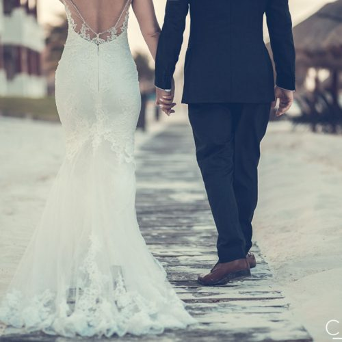 Close up of bride and groom walking away on wooden path