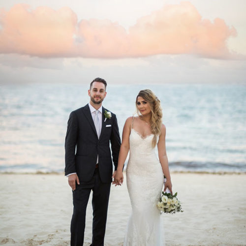 Portrait of bride and groom in front of Caribbean sea.