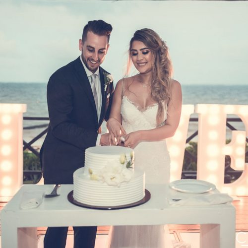 Bride and groom cutting cake with ocean in background.