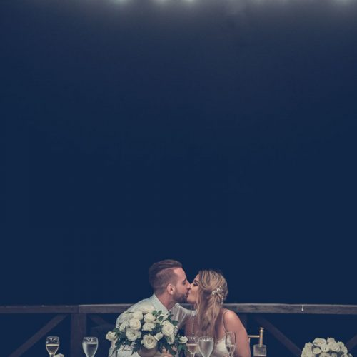 Bride and groom kissing at wedding reception.