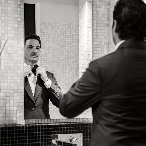 Groom doing up tie in front of mirror at Banyan Tree Mayakoba