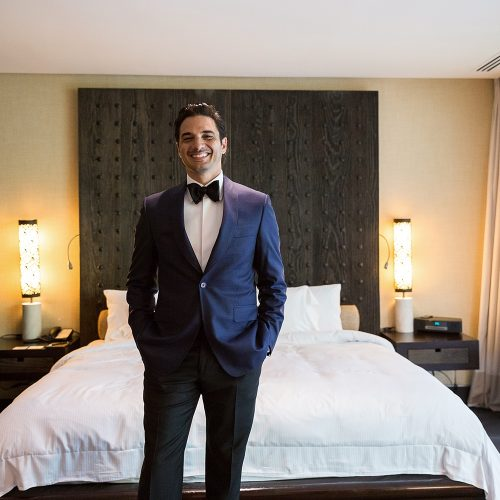 Portrait of groom in front of bed at Banyan Tree Mayakoba