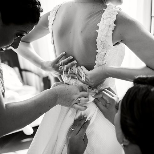 Close up of bride having her dress done up before wedding ceremony.
