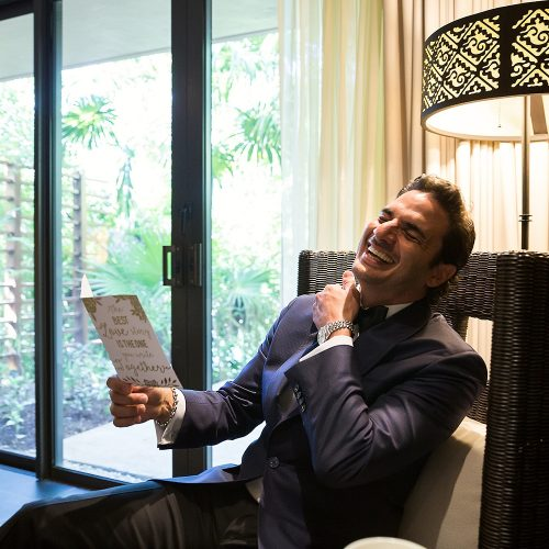 Groom laughing at card.