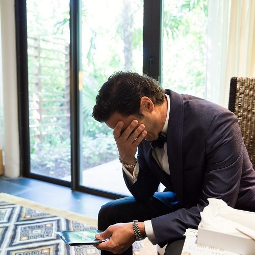 Groom crying over card.