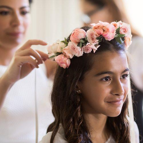 Bride putting flowers on flower girl before wedding ceremony