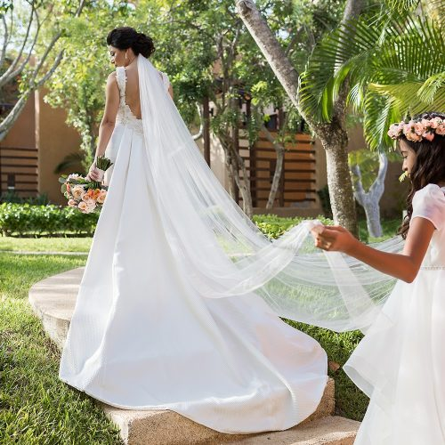 Bride with flower girl holding her veil on way to ceremony at Banyan Tree Mayakoba