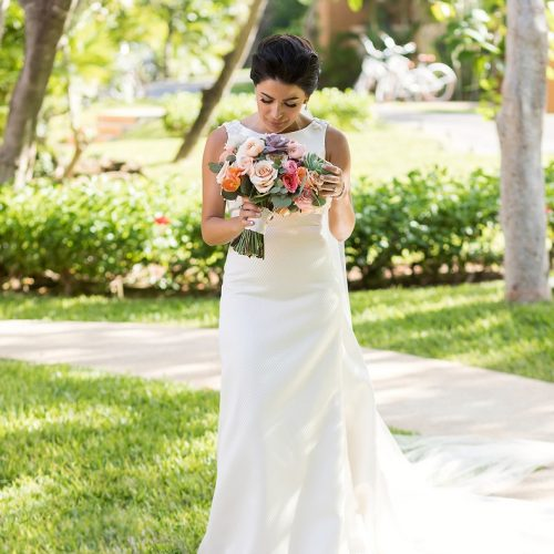 Portrait of bride looking at flowers before ceremony at Banyan Tree Mayakoba