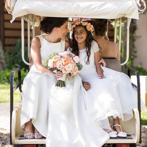 Bride and flower girl on back of golf cart.