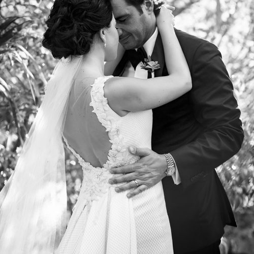 Bride and groom in romantic pose in black and white.
