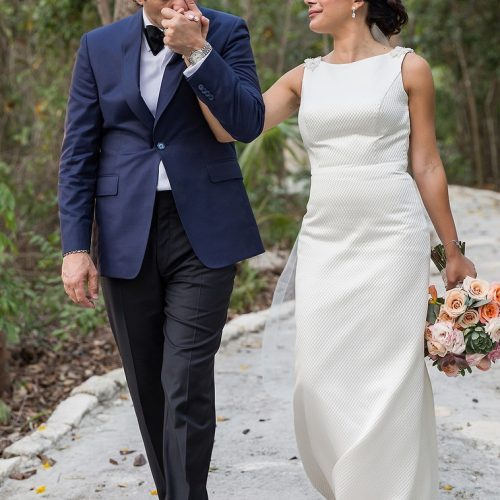 Groom kissing brides hand while walking.