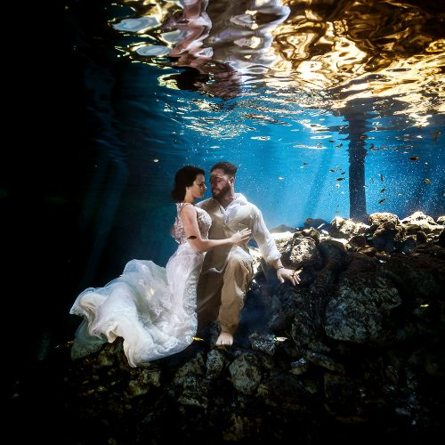 Bride and groom underwater in cenote on Mexico