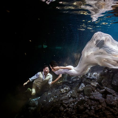 Bride swimming towards groom in mayan cenote TTD.