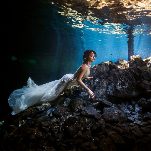 Bride underwater fashion in bridal dress.