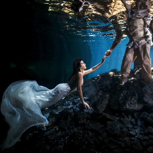 Bride holding grooms hand in underwater trash the dress (TTD)