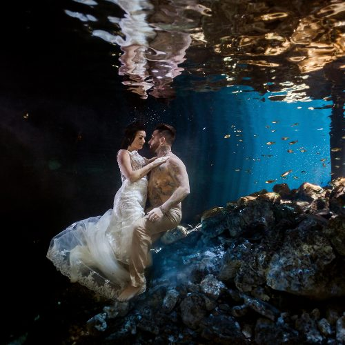 Bride and groom kissing underwater in Trash the Dress (TTD).