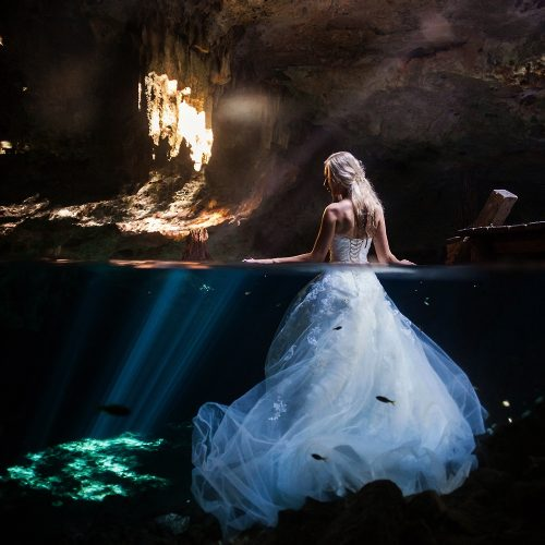 Bride half in and half out of water at Cenote Trash the Dress
