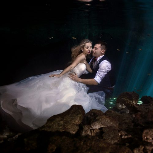 Bride and groom in romantic pose underwater in mayan Cenote Trash the Dress