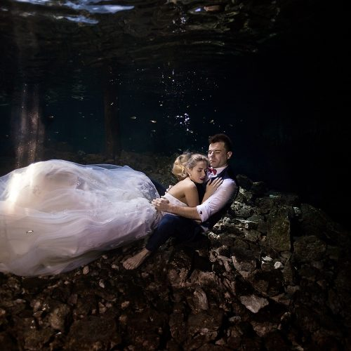 Bride laying on groom underwater in cenote TTD