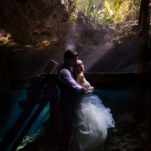 Bride and groom half underwater and above in romantic pose in Cenote Trash the Dress
