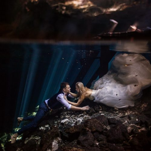 Bride and groom swimming together in Cenote Trash the Dress
