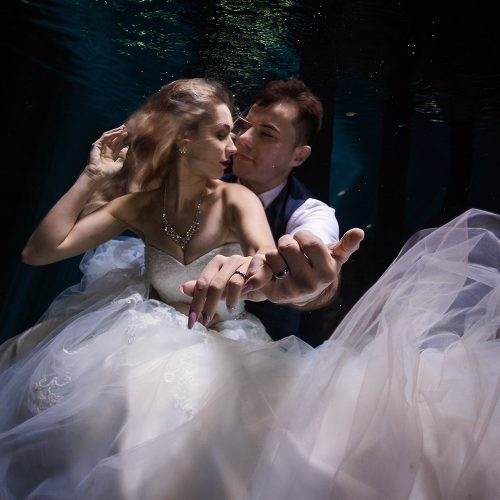 Bride and groom showing rings in Mayan Cenote Trash the Dress