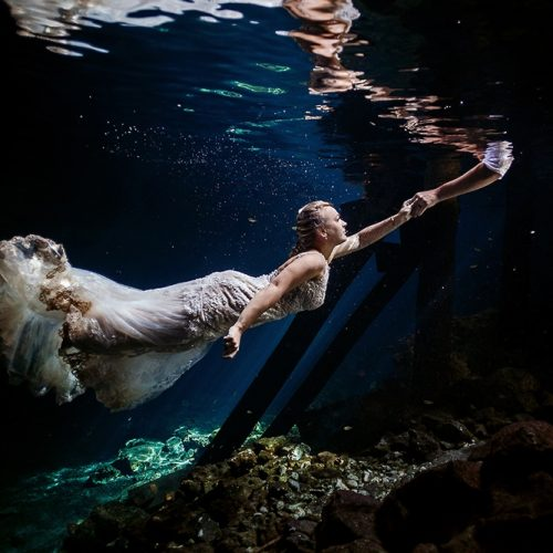 Bride reaching for grooms hand in underwater Mayan Cenote Trash the Dress