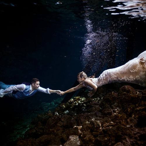 Bride and groom underwater reaching for each other in Mayan Cenote Trash the Dress