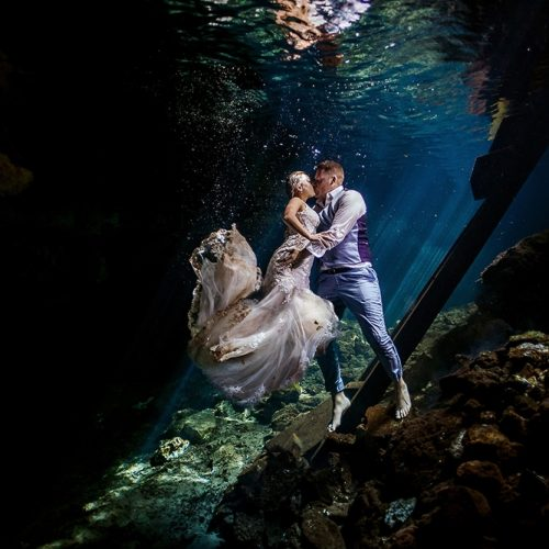 Bride and groom kissing underwater in Mayan Cenote Trash the Dress