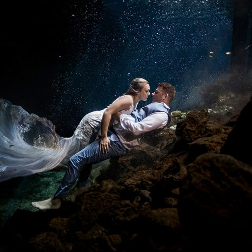 Bride and Groom underwater in romantic pose.
